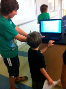 a younger and older elementary student working together on a laptop