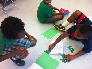 3 students working on math problem-solving on the floor